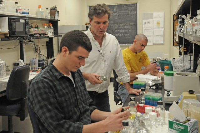 Jeff Arace '12, pictured in the foreground, and Ph.D candidate James Arnone, pictured in the back, work on transcriptional regulation of paired genes involved in ribosome biogenesis with their advisor, Michael McAlear, chair and associate professor of molecular biology and biochemistry, in center. Adam Robbins-Pianka BA '08, MA '10 and Sara Kass-Gergi '12 also work in the McAlear Lab.
