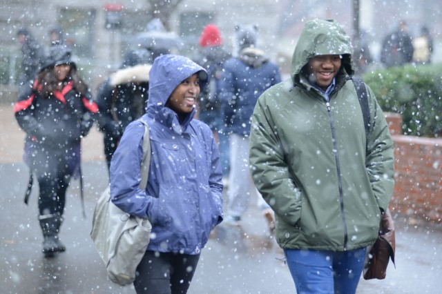 Simone Greene '13 and Isaiah Sypher '13 walk near the Public Affairs Center during the afternoon snowfall.