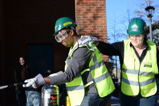 """C-CERT trainees Frantz Williams, director of parent relations, and Kathleen Roberts, residential operations coordinator, use the """"buddy system"""" to suppress a fire."""