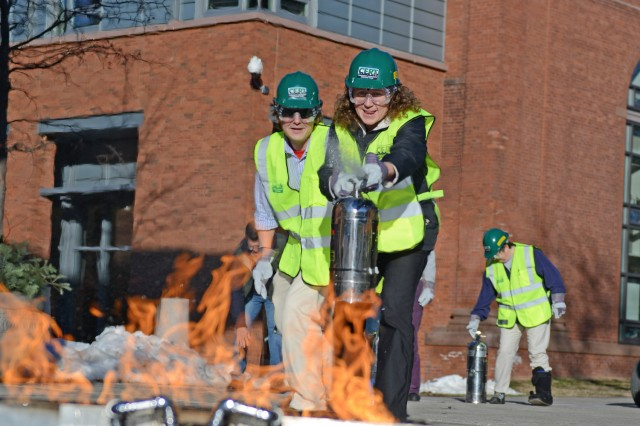 Sherri Condon, accounting specialist, and Mark Grabulis, ITS events temporary employee, learn to use a fire extinguisher at C-CERT training.