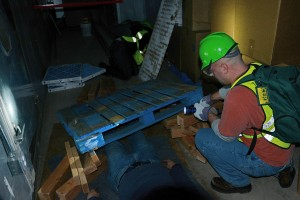 Vinnie Agosta, desktop support specialist, uses leveraging and cribbing to remove a trapped victim during C-CERT training.