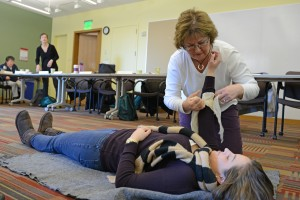 Kris McQueeny, administrative assistant for the Theater Department, practices how to stop bleeding and apply a bandage during C-CERT training.