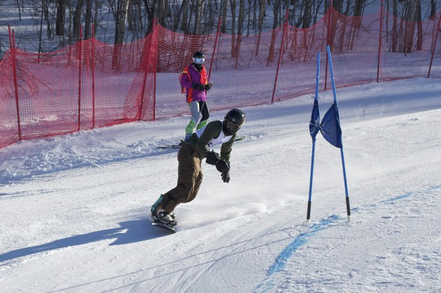 Dylan Penn '15 leans into the turn of a snowboard Giant Slalom race at the Middlebury College Snow Bowl.