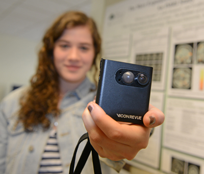 Tacie Moskowitz 13 holds the memory camera used in the lab's study. The camera is worn around a person's neck and automatically takes photos when it senses motion and changes in light color, light intensity and temperature. 