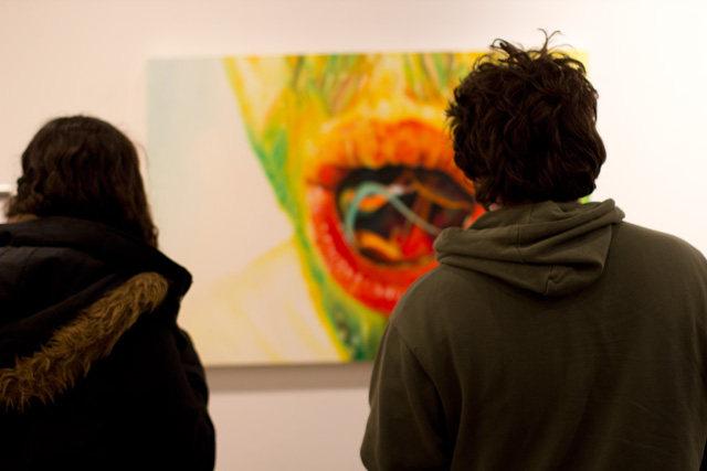 Gallery goers admire a painting.