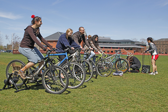 Students ride bikes to generate power for a concert at Earth Fest, a music and food festival that took place on Foss Hill on April 21.