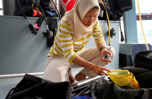 Intan Suci Nurhati '05 prepares equipment for coral drilling. By researching Singapore's corals, she hopes to gain insight into climatic changes in the region. (Photo by Alex Westcott/TODAY)
