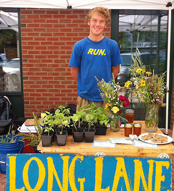 Coady Johnson '15, who is double majoring in astronomy and physics, tends a booth at the North End Farmers' Market, where he sells produce from Wesleyan's Long Lane Organic Farm. Johnson is one of 10 student farmers working at Long Lane this summer. After graduating, Johnson hopes to study astrophysics and ultimately become an astronaut.