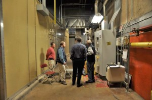 "The Central Power Plant team discusses the performance of the main ""island mode"" generator, located behind the wall on the left."