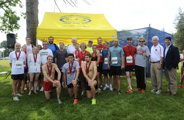 Pictured, front row, from left, are Matt Franco '07, Bryan Marsh '13 and Alex Battaglino '07. Pictured, back row, from left, Kevin Markowski '79, Barrie Robbins-Pianka, Judy Goodale, Richie Marshalek, Cross Country Coach John Crooke, Elmer Swanson, Sherri Condon, Sharon Purdie '74, John Hastings '71, Tia Accetta, Amby Burfoot '68, Christopher Caesar, James Taft, Bill Rodgers '70, John Driscoll '62 and Daniel Drew, Mayor of Middletown.