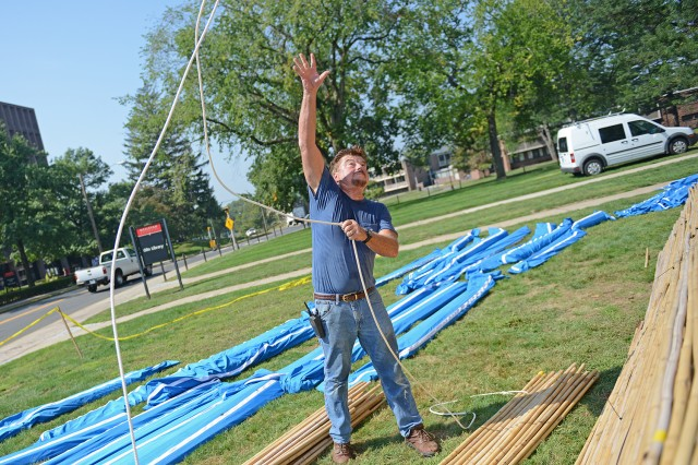 Journeyman Carpenter Paul Marin used a rope to hoist the bamboo sections to the sukkah's top.
