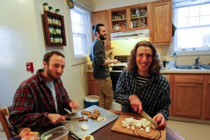 From left, Jon Lubeck, prepares a meal with co-op co-organizers Scott Zimmer '14 and Will Curran-Groome '14.