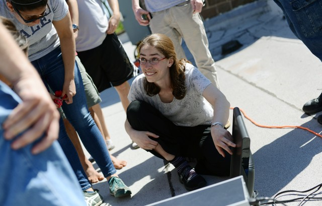 Meredith Hughes, assistant professor of astronomy, works with students on a small radio telescope, located on the roof of the Van Vleck Observatory.