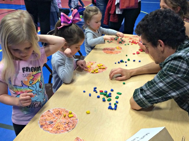 Davey Bales '15 and Julia Vermeulen '15 play a math game with Eliana, Carly and Sam at Family Math Night.