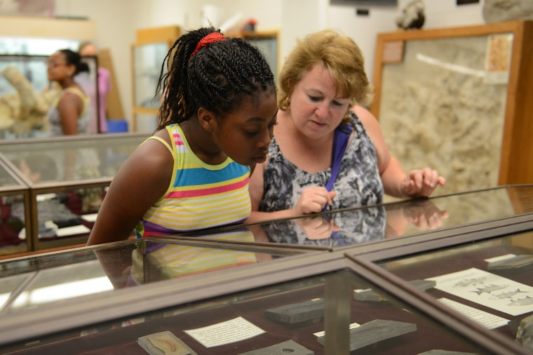 A student and her teacher, Ms. Thompson, look over Connecticut Valley Jurassic Fossils.