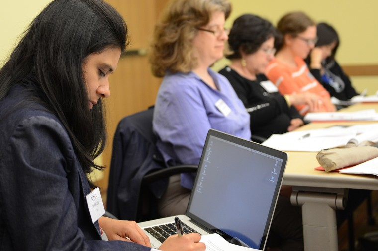 A conference participant takes notes during the poetry session.