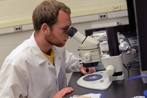 By using a microscope in Wesleyan's Solar Systems Geochemistry Lab, Jack Singer takes a closer look at a Lunar sample.