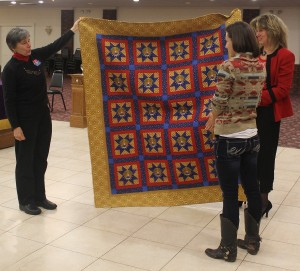 Kyle Foley receives the Quilt of Valor from Jane Dougherty, the Connecticut Quilt of Valor representative, and Deborah Sierpinski, administrative assistant at Wesleyan.