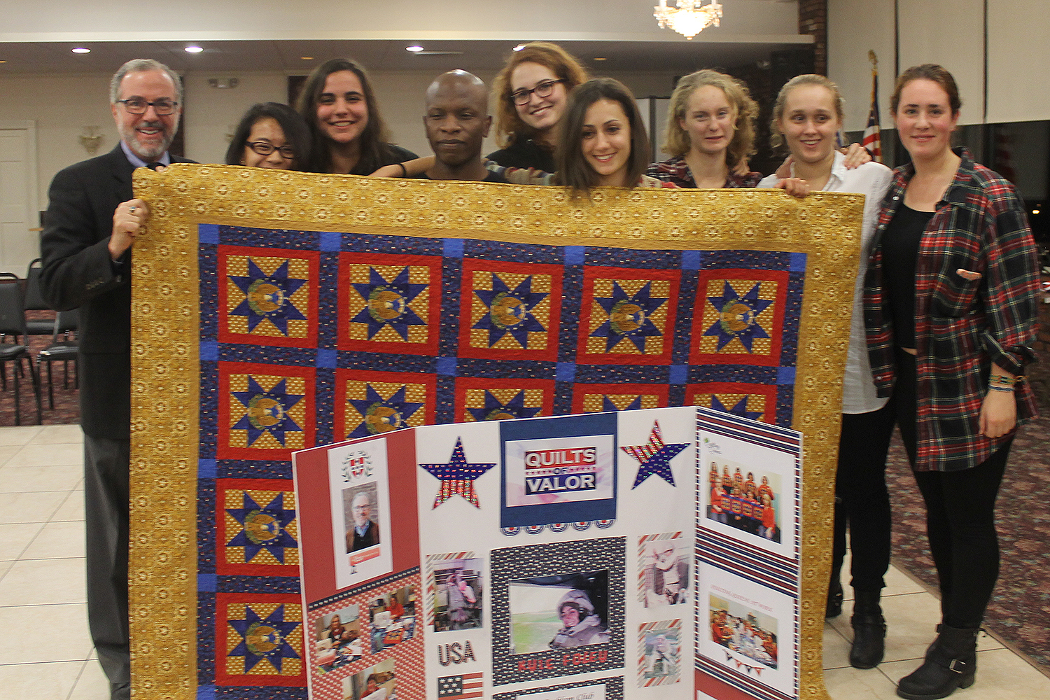 Kyle Foley '18 received a Quilt of Valor Dec. 3 at the Emblem Club in Middletown. She's pictured here with several Wesleyan students and at left, Professor Andy Szegedy-Maszak.