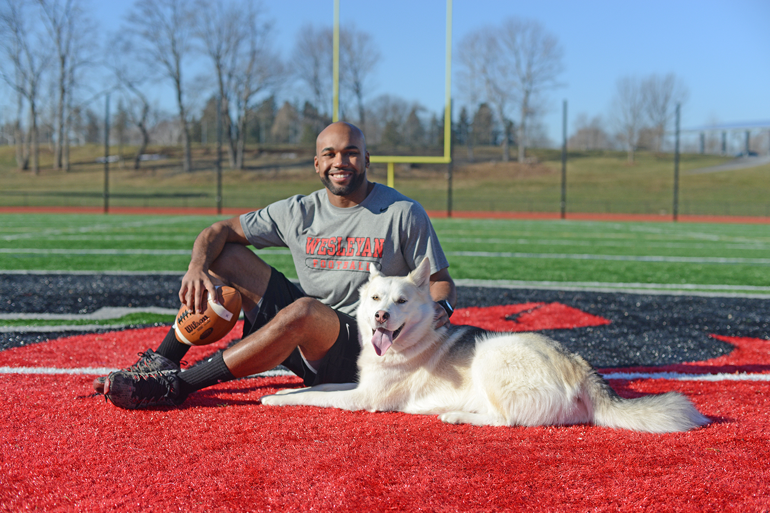 "Jay Fabien '15 and his ""rescued"" husky, Glacier, hang out on Citrin Field Jan. 23. Fabien, formerly a wide-receiver for the Wesleyan Cardinals Football Team, hopes to coach student-athletes after graduation and later join the U.S Army Special Forces."