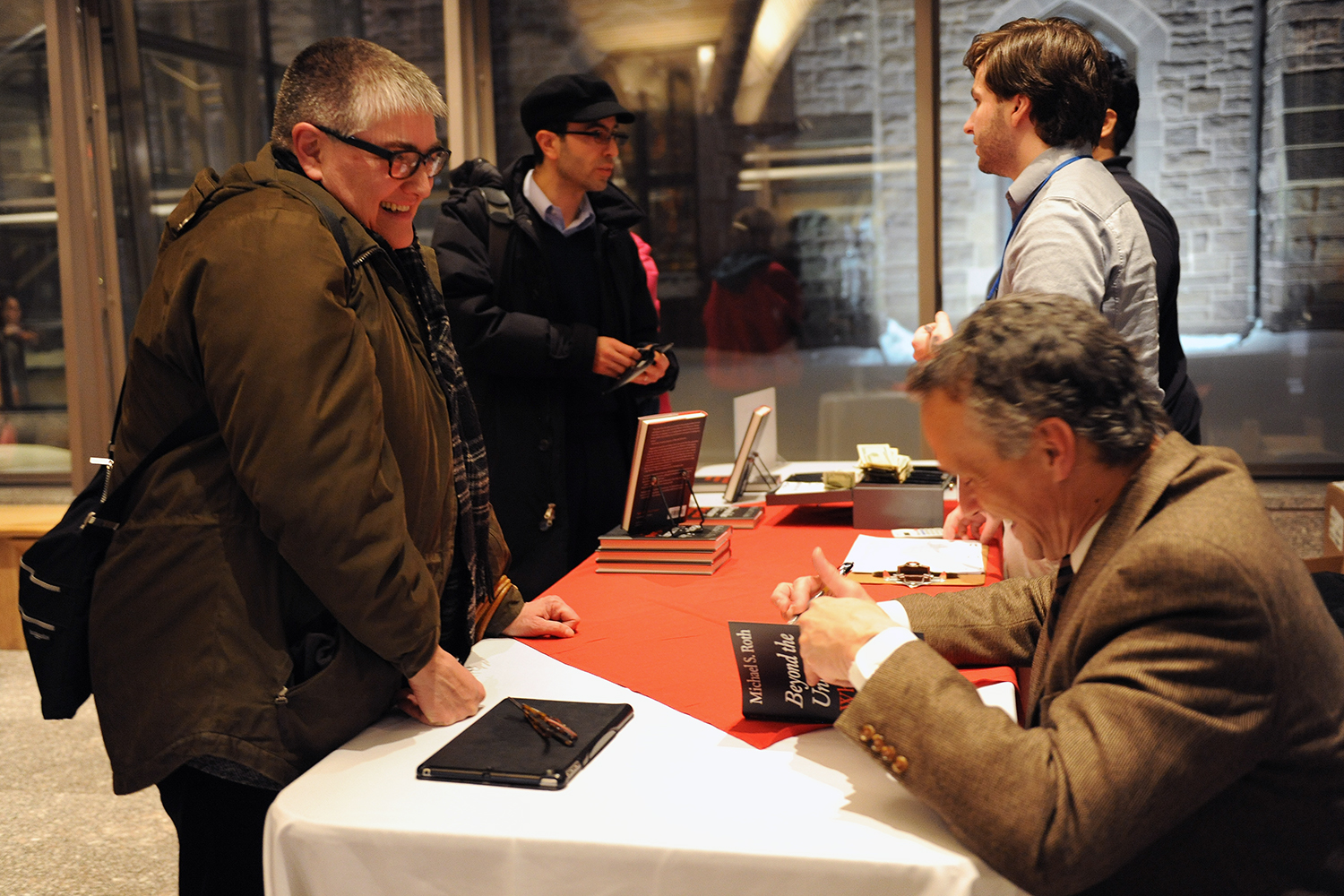 Roth signs his book <em>Beyond the University: Why a Liberal Arts Education Matters</em> for an attendee.  All royalties go to Wesleyan's financial aid.