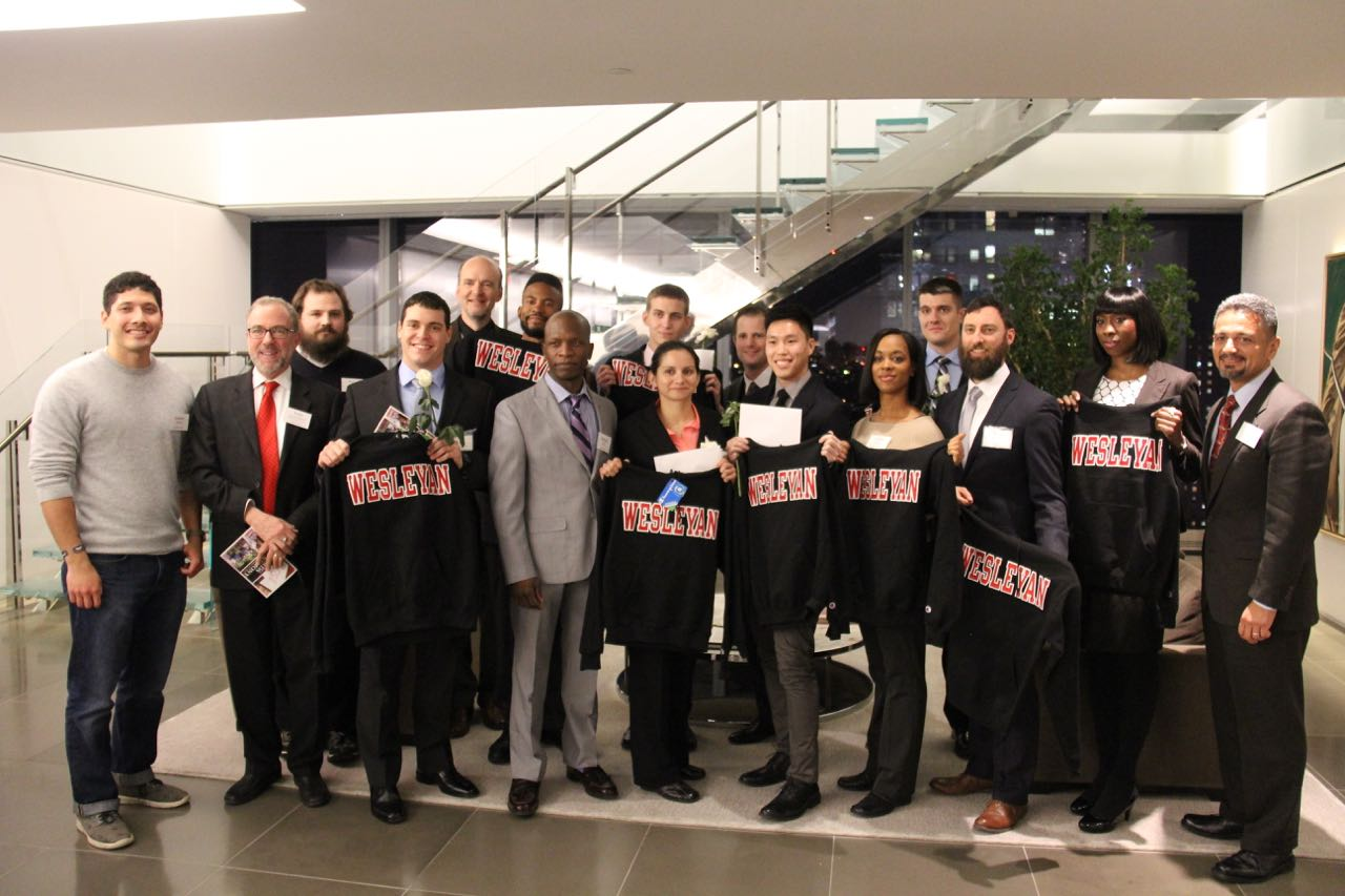 The newly accepted class of Posse Veteran Scholars, holding Wesleyan shirts, together with some current Posse scholars. Also shown are Andy Szegedy-Maszak, faculty mentor of the Class of 2018 Posse scholars, and Jane A. Seney Professor of Greek; John Gudvangen, associate dean of admission and financial aid/director of financial aid; and Antonio Farias, vice president for equity and inclusion/ Title IX officer.