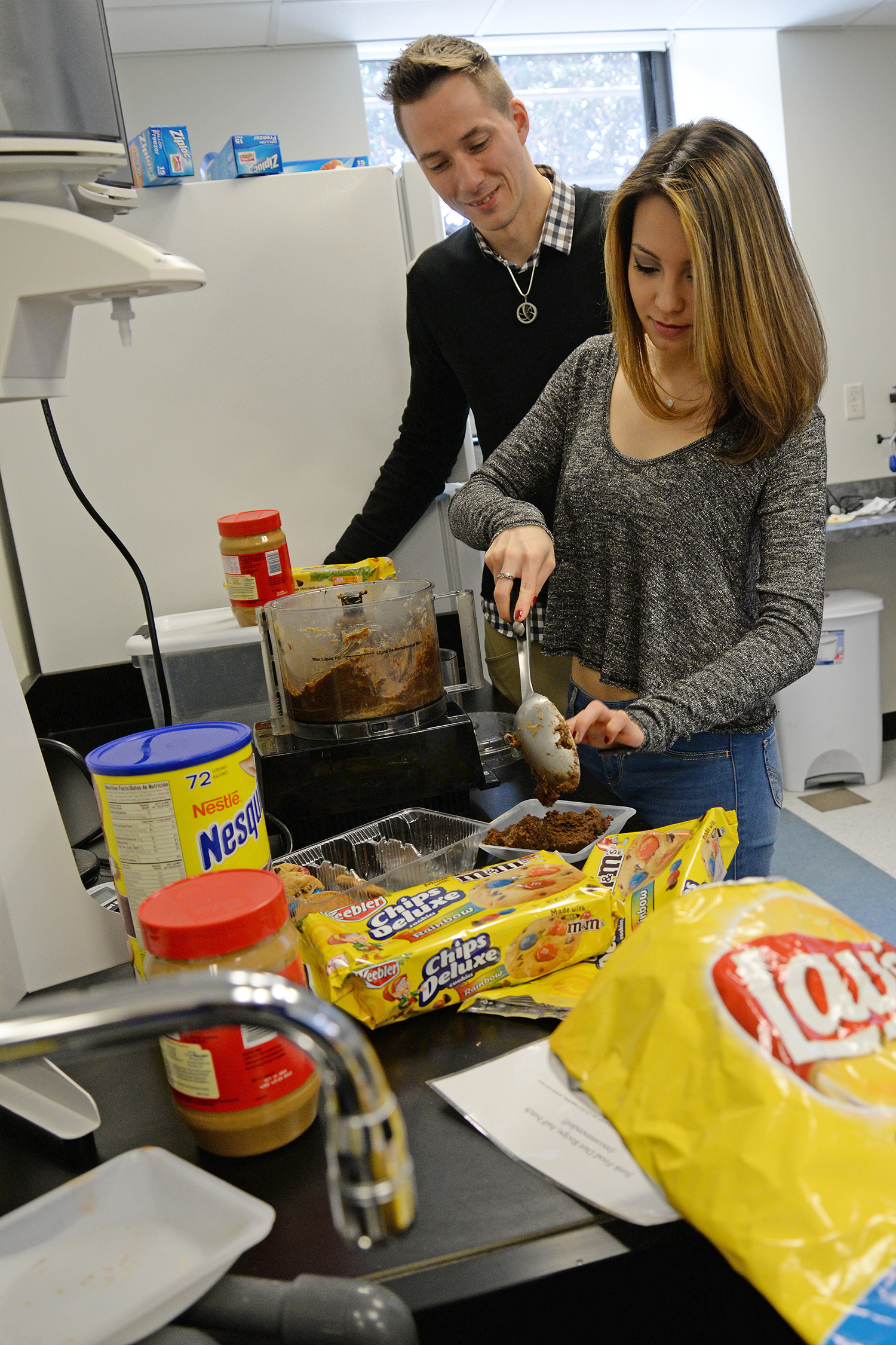 Mike Robinson and Rebecca Tom '16 remove the junk food concoction from the food processor.
