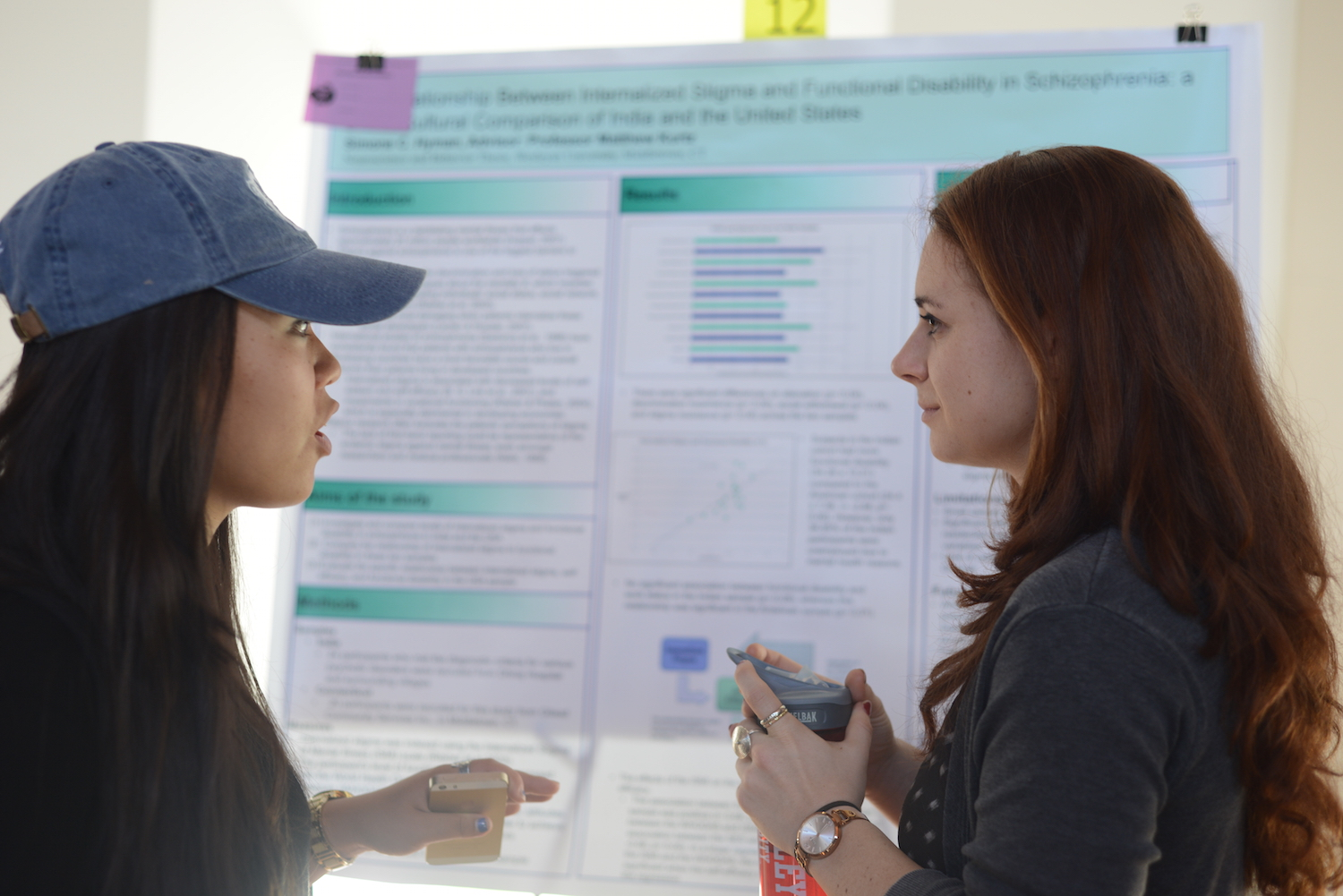 "Simone Hyman '15, right, discusses her research on ""The Relationship Between Internalized Stigma and Functional Disability in Schizophrenia: A Cross-Cultural Comparison of India and the United States"" with another psychology major, Sarah Seo '16."