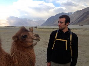 Greenwald with a camel in front of the Zangskar mountain range.