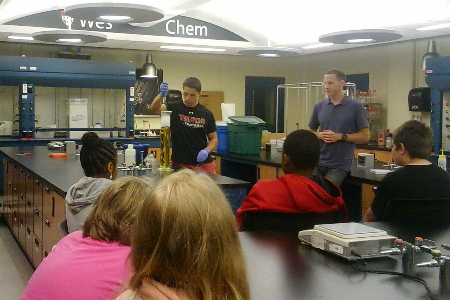 Brian Northrop, assistant professor of chemistry, and Snow School students watch chemistry in action during their visit to Wesleyan. This annual program allows local fifth graders to see how science can be exciting as well as educational.