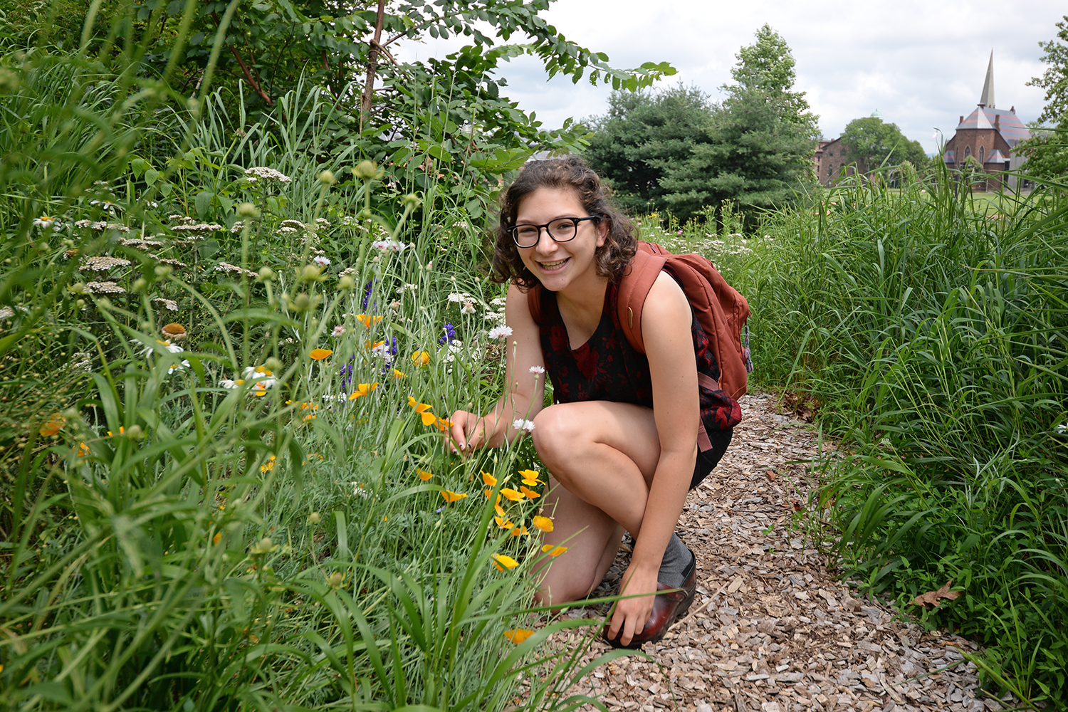 "Heather Whittemore '17, who is working on campus this summer, enjoys occasional strolls through the WestCo. courtyard. ""I like to check out what's blooming,"" she said."