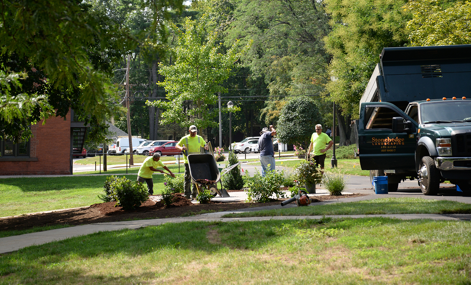 Crews lay mulch and plant shrubs and perennials at a patio across from Judd Hall on Aug. 24.
