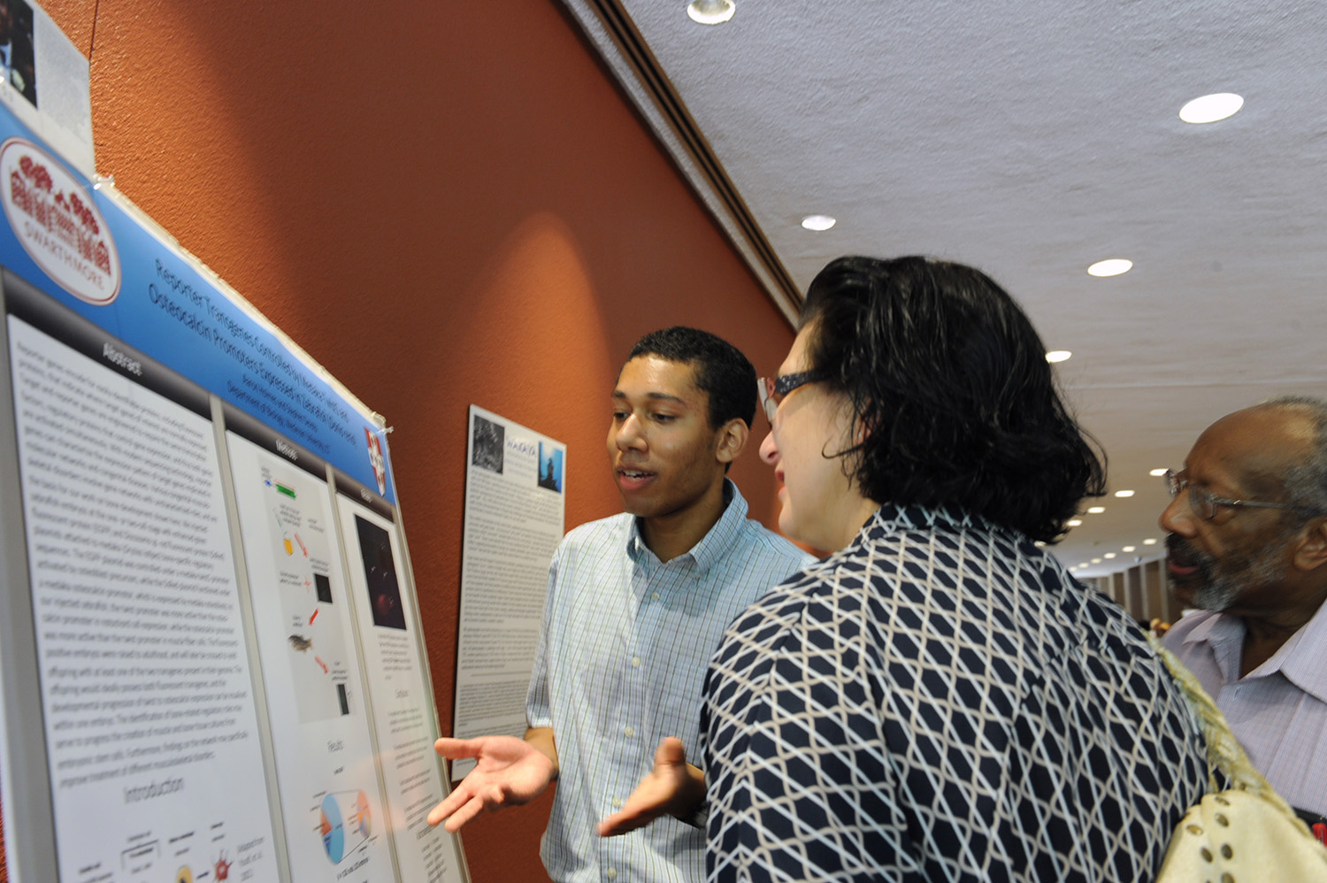 "Aaron Holmes 'xx talks to onlookers about his poster, ""Reporter Transgenes Controlled by Bone-specific Medaka Promoters Expressed in Zebrafish (Danio rerio)."" Holmes' faculty adviser is Stephen Devoto, professor of biology, professor of neuroscience and behavior."