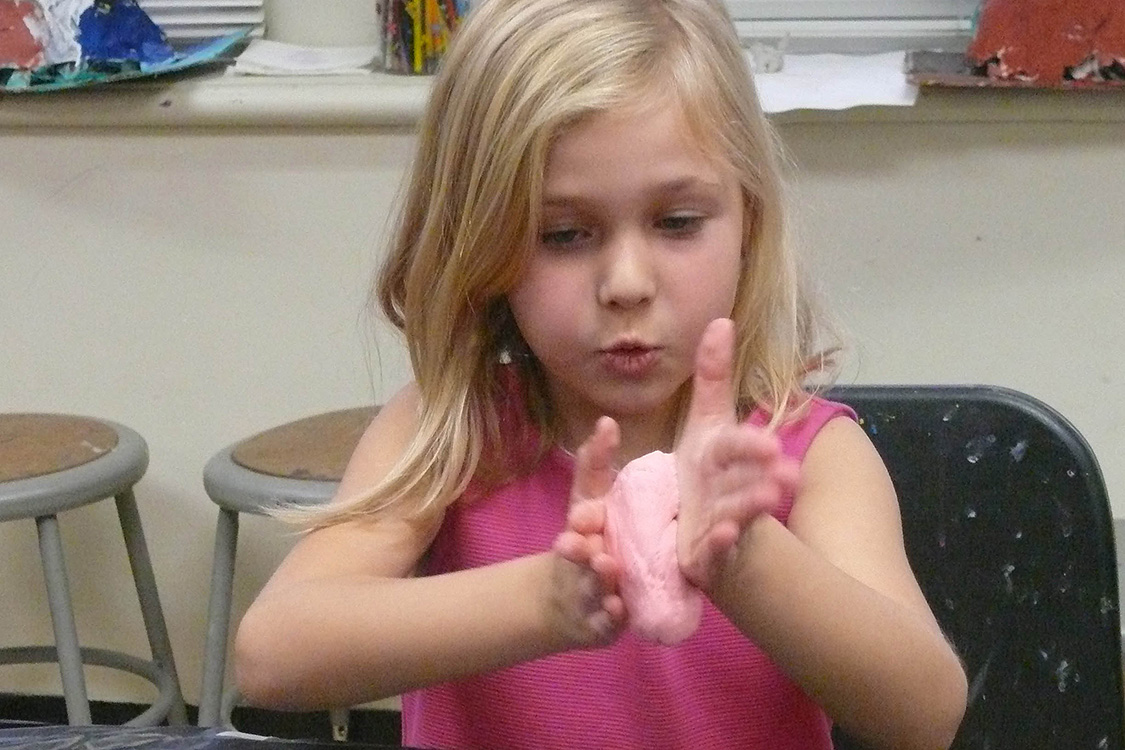 "Darcey Northrop, the daughter of Brian Northrop, gets her hands in some gak. ""The students were delighted with their efforts in learning about viscoelastics and in stirring up some gooey gak,"" said Sandra Guze, GSTLC education and program coordinator."
