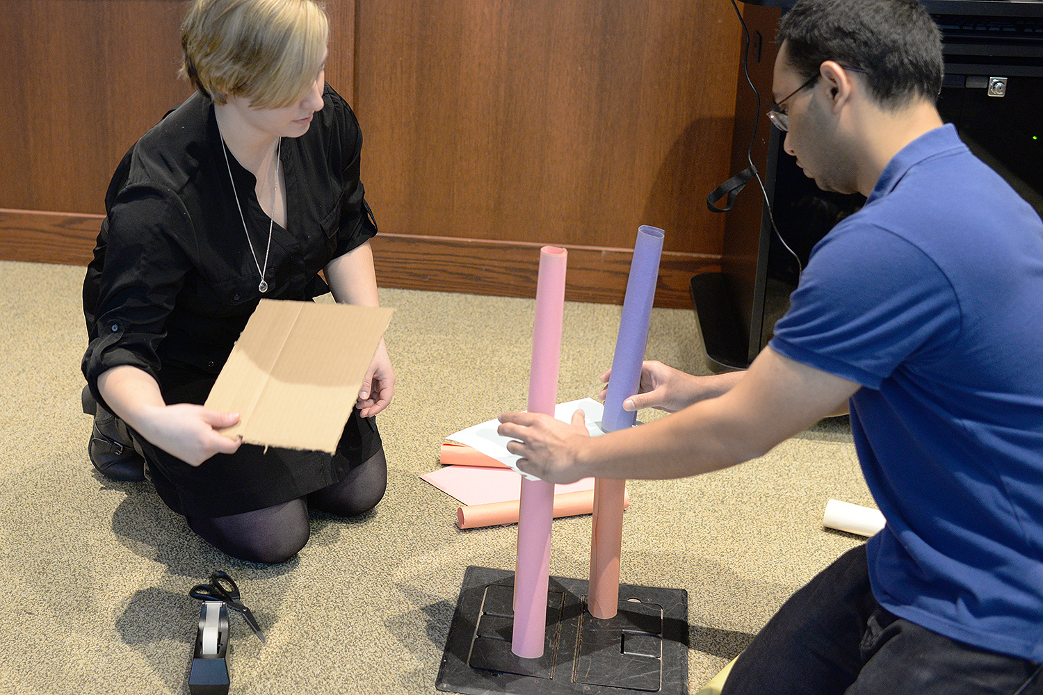While working in groups of three and four, the teams each had five minutes to plan how they'd construct a 5-foot-tall, free standing structure using only paper, two sheets of cardboard, tape and scissors.