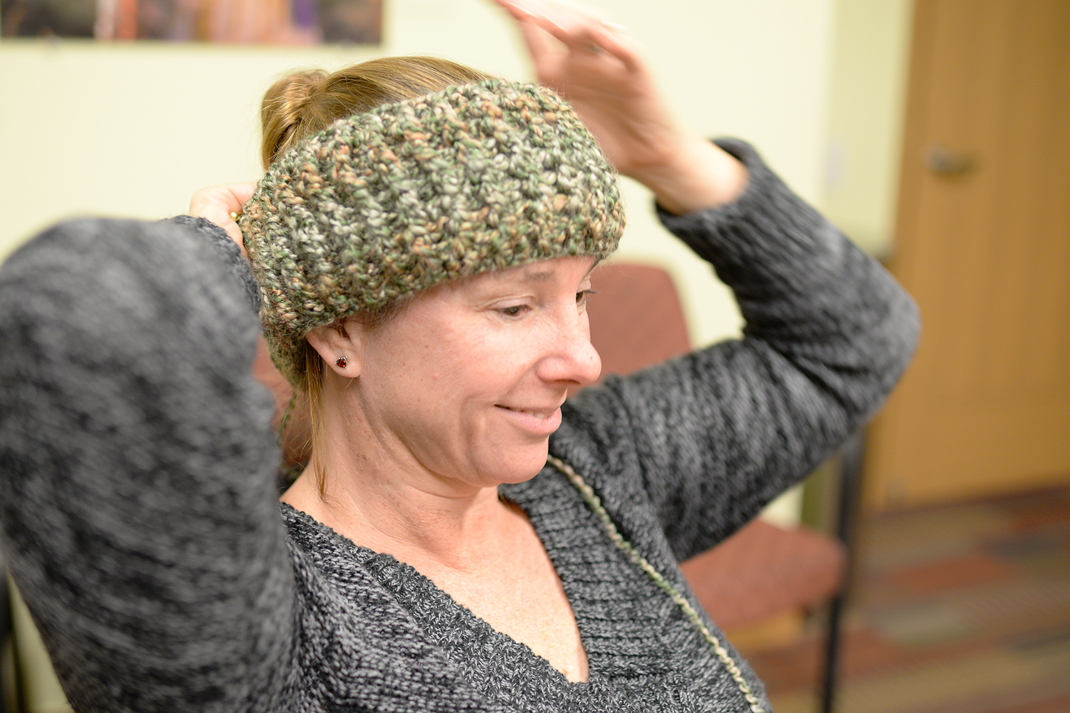Amy Alfano, administrative assistant for Residential Life, tests out her latest crochet project.