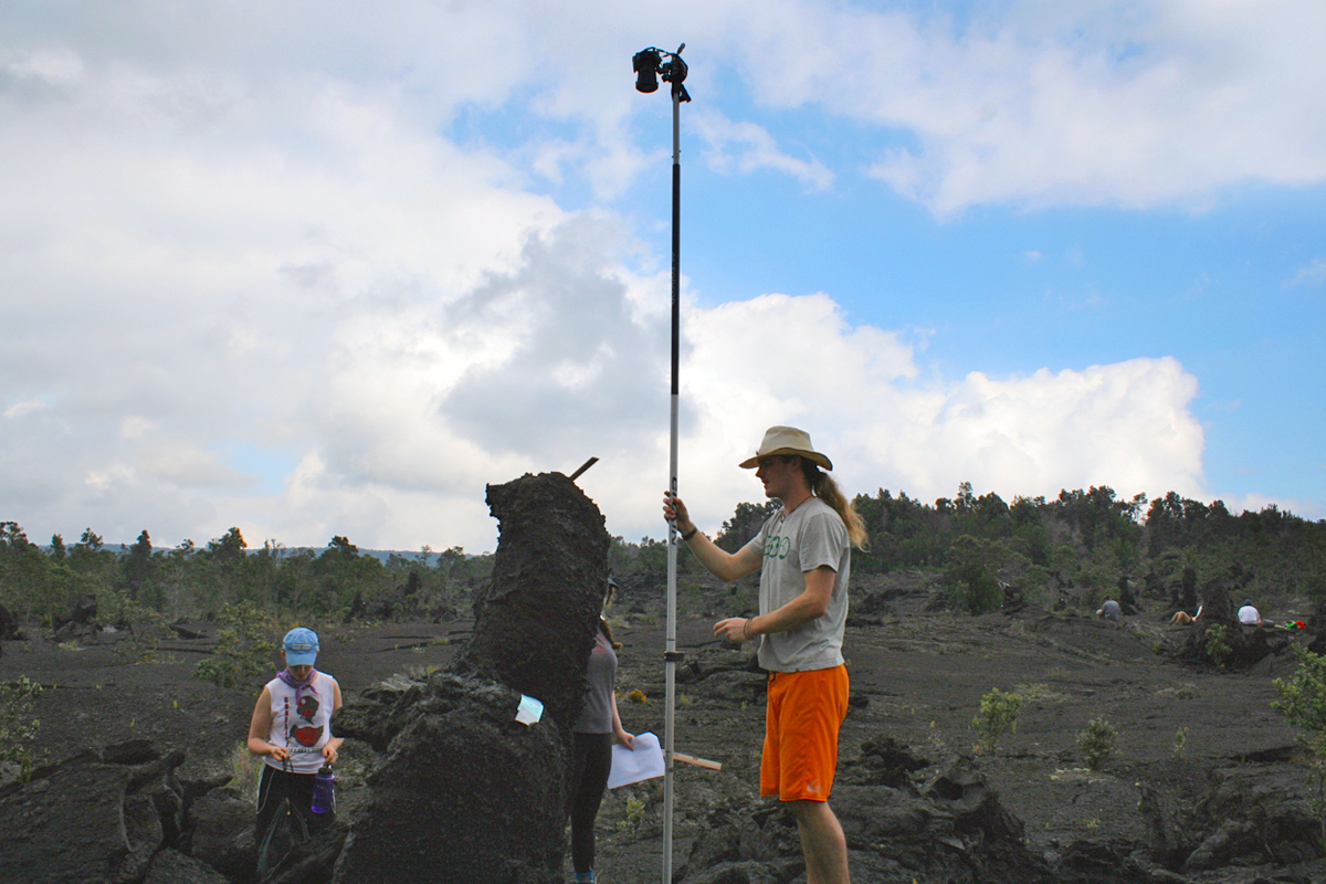 "Will Sawyer '16 uses a long ""selfie stick"" to photograph a top view of lava tree mold on a 1974 lava flow while Dara Mysliwiec '16 and Alex Fireman'16 assist."