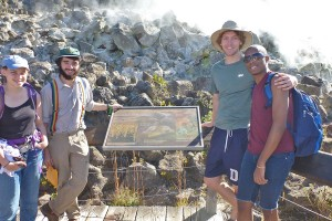 Students gather near the Hawaii National Volcanoes Park sign and sulfur springs.