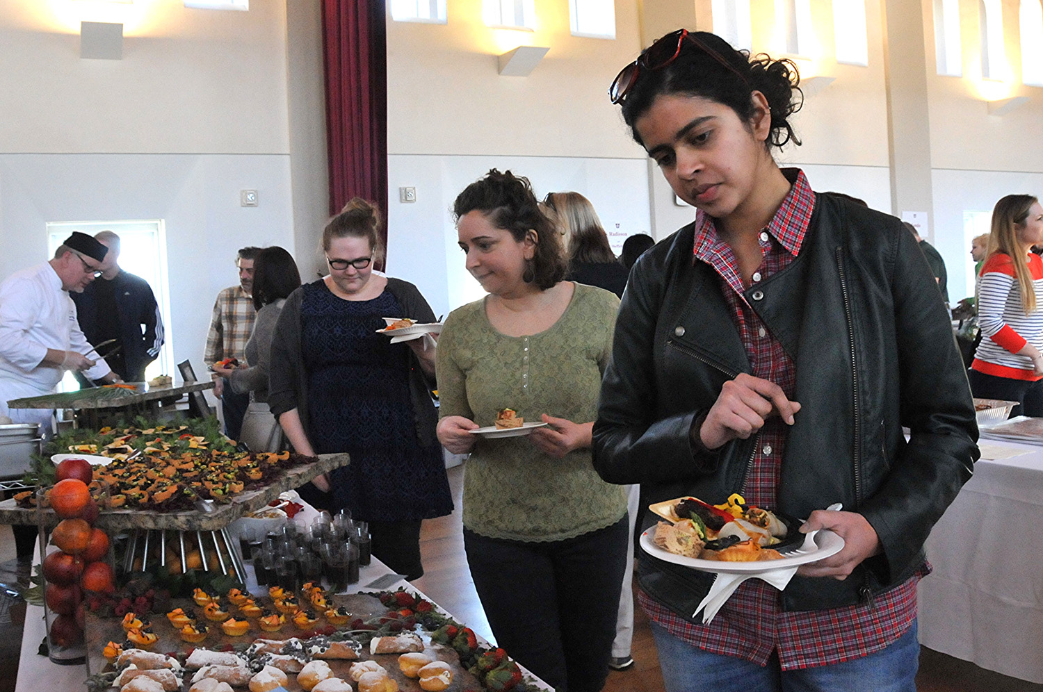 Natasha Kini, assistant director of online communications for University Relations, and others peruse the dessert spread.