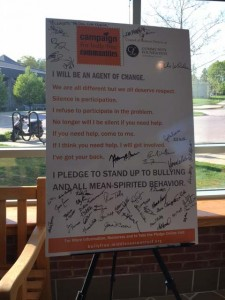 The poster with the pledge to be an agent of change is filled with signatures.