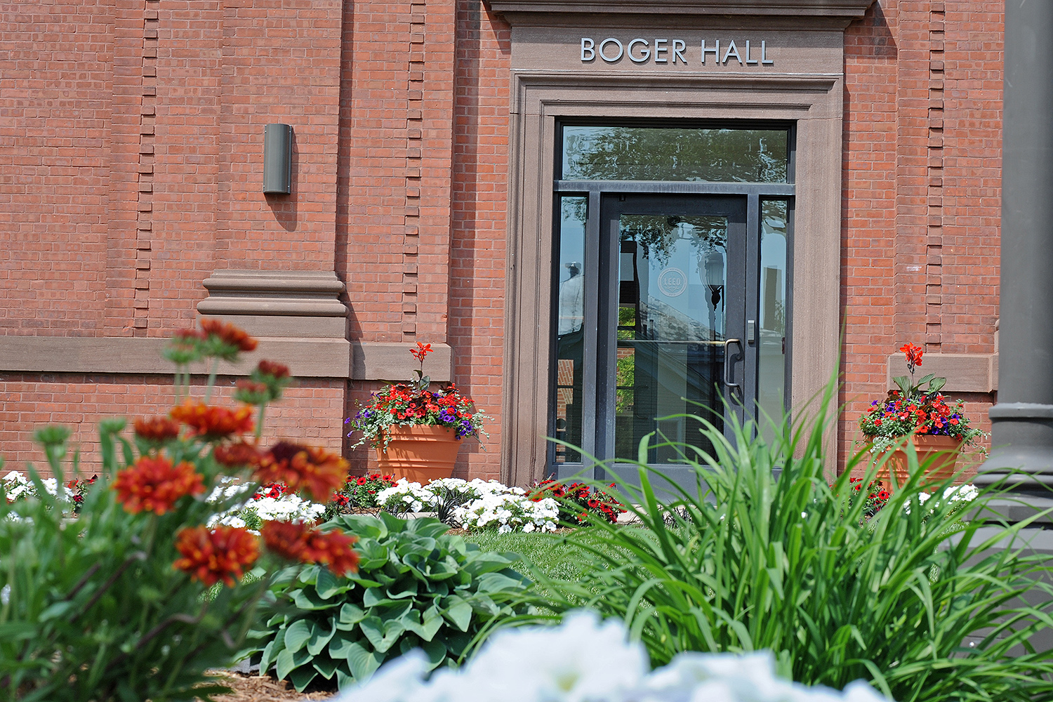 Petunias, geraniums and other flowers are planted near Boger Hall.