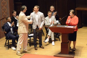Jed D. Hoyer '96 stands on stage and president Roth shakes his hand while Daphne Kwok '84 looks on.