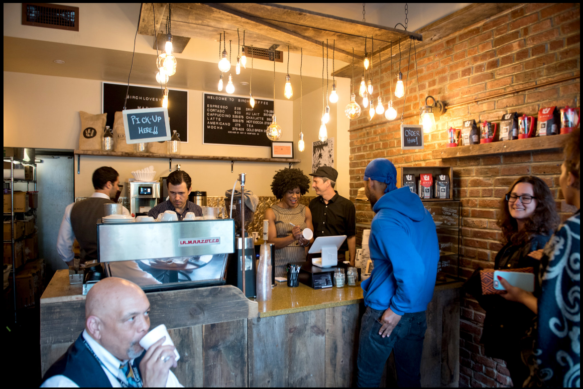 Majora Carter '88, center, marks a coffee cup, as she takes an order at the Birch coffee shop she and her husband recently opened in the South Bronx. Photo credit: Edwin J. Torres for The New York Times See the photo series>