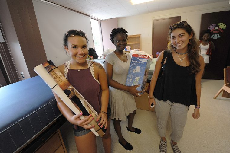 Cassie Morales '20 from Oceanport, NJ, Malika Ilboudo '20 from the Bronx, and Shiri Benmoshe '20 from Manhattan begin unpacking and rearranging furniture with help from their families.