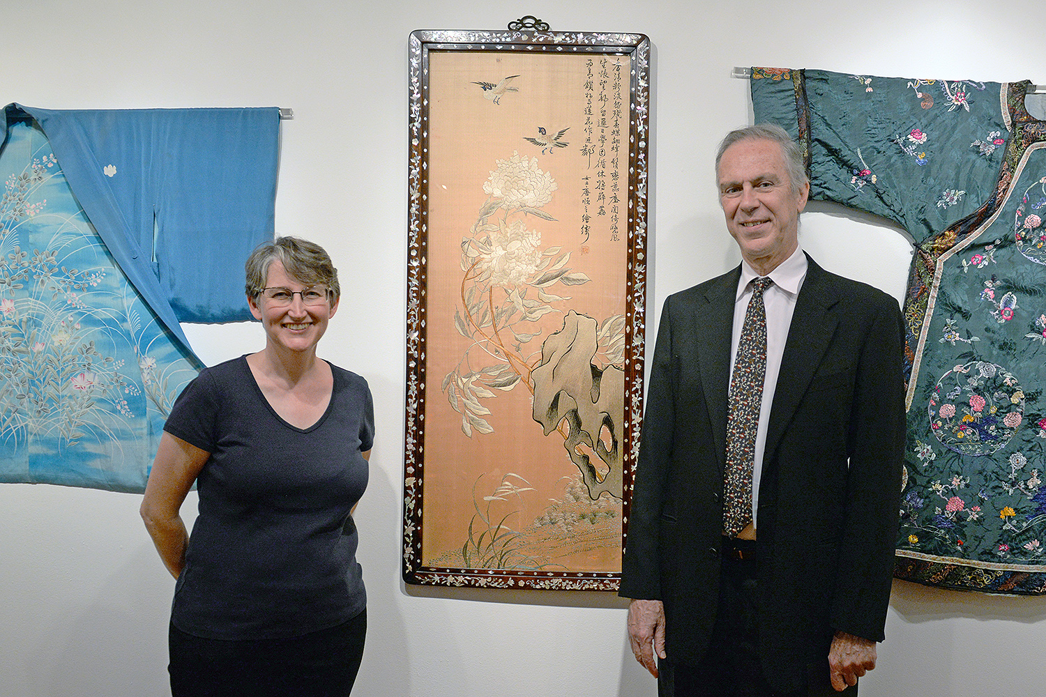 "Clare Rogan, curator of the Davison Art Center, and Patrick Dowdey, curator of the Freeman Center for East Asian Studies stand near a silk embroidery titled ""Peony (pre 1925)"" from Southeast China. The artwork is framed in hardwood with a mother of pearl inlay."