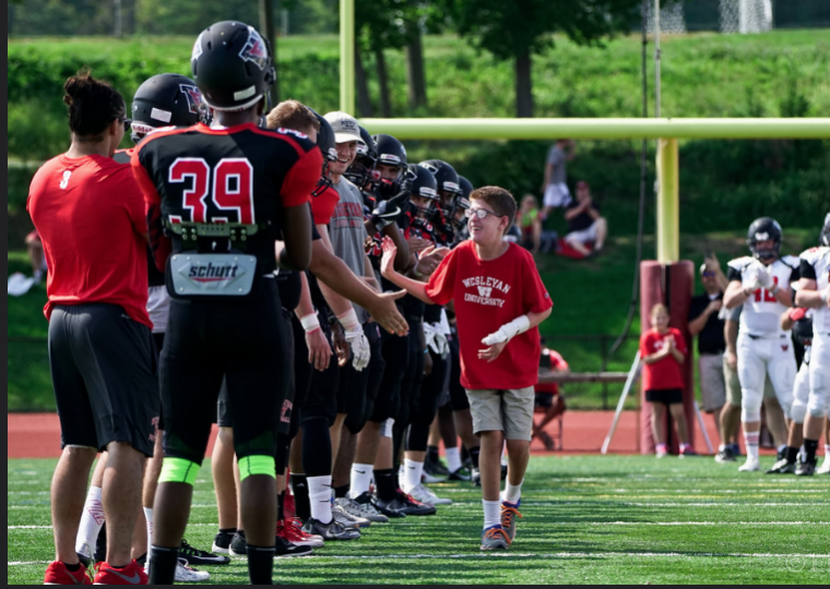 Michael receives high-fives and handshakes from the Wesleyan football team.