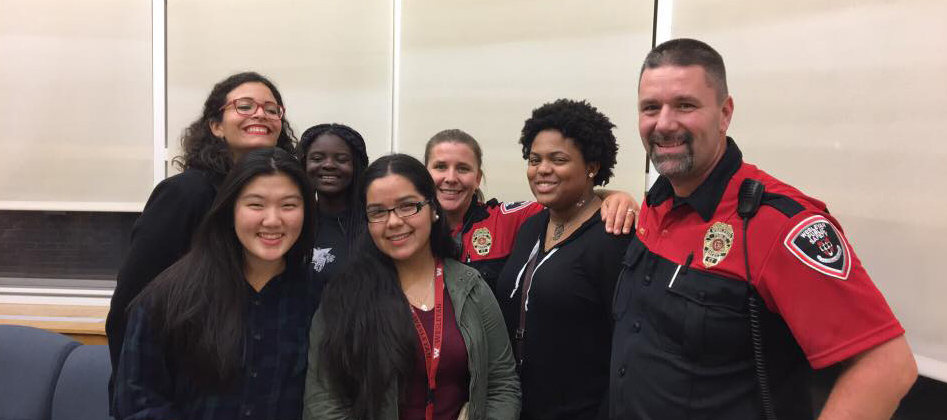 "At right, Public Safety Supervisor Lt. Fred West and Officer Kathy Burdick, center, gather with Wesleyan students in Bennet Hall during ""Pancakes with P-Safe."""
