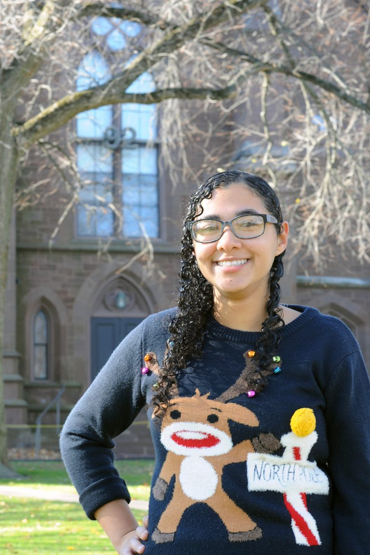"May Treuhaft-Ali '17, donning a reindeer sweater she acquired from a study abroad experience in Ireland, poses near the '92 Theater where she ""spends half her time."" Treuhaft-Ali recently was awarded a Mitchell Scholarship to study theater and performance in Dublin."