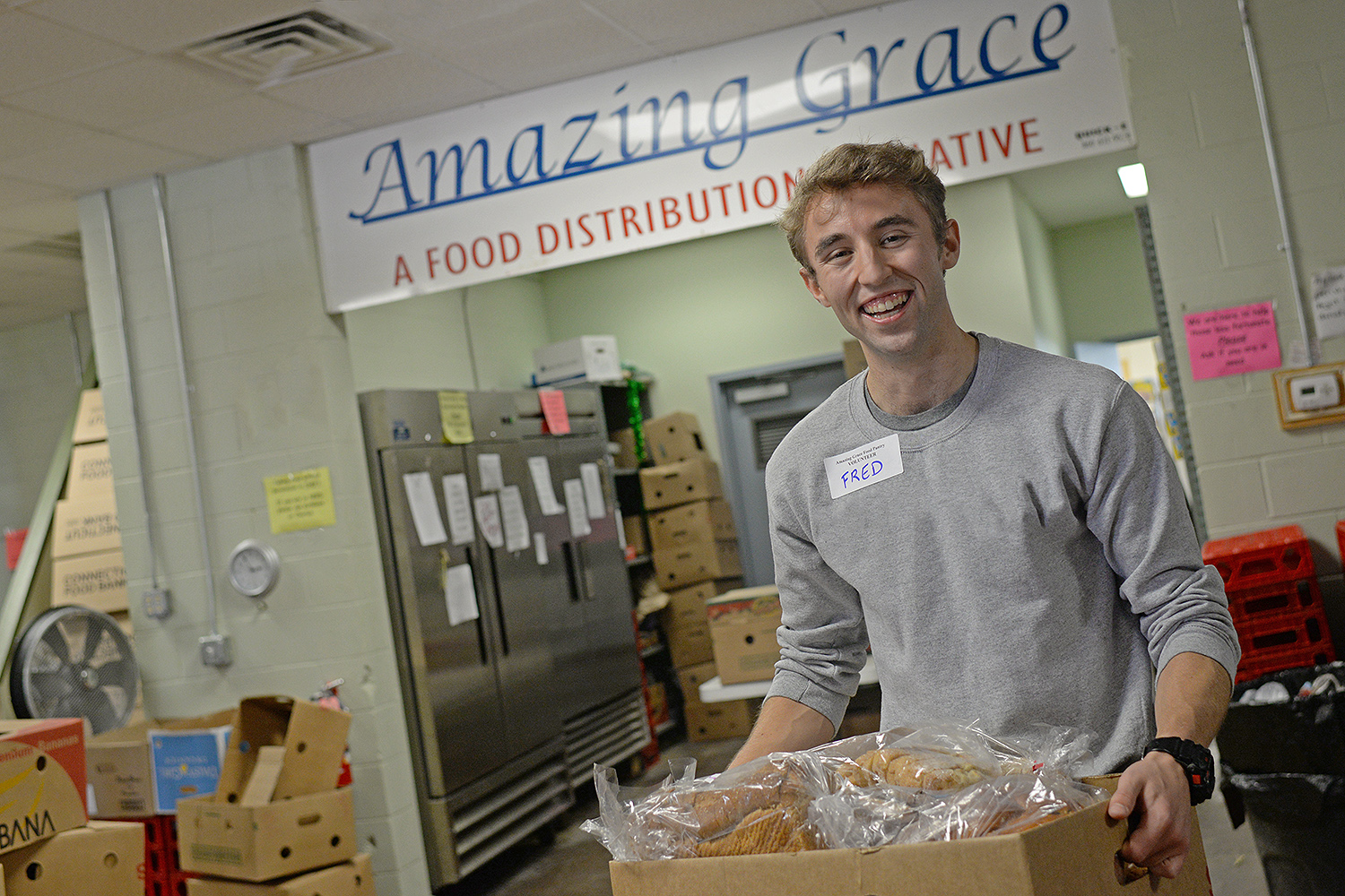 Fred Ayres '17 helps stock shelves at Amazing Grace Food Pantry in Middletown on Oct. 4. Ayers is one of several Wesleyan students and alumni who are volunteering at the food pantry this month.