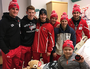 Hockey players visit Connor in the hospital.